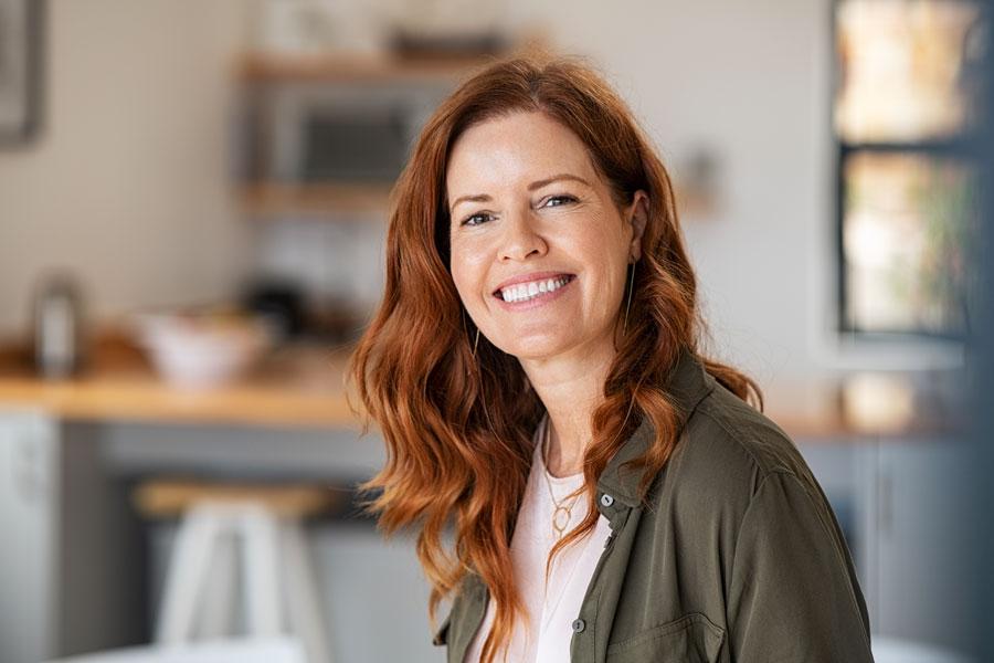 vrouw met rood haar en mooie huid in de keuken